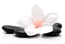 Picture of a massage stones with a white flower on top